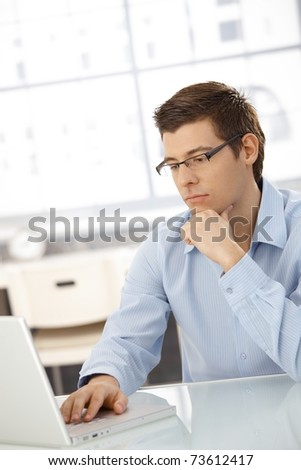 Young businessman concentrating on computer work, looking at laptop screen, thinking.?