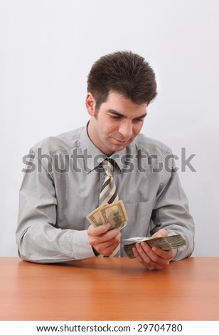 Young businessman counting US paper currency with sitting at the table.