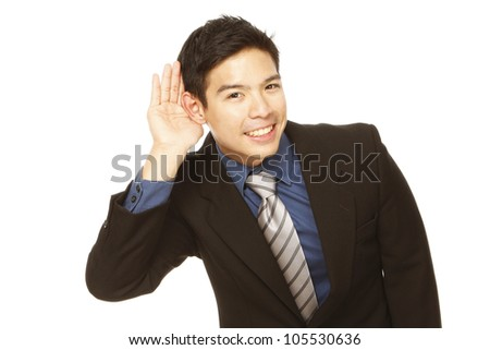 Young businessman cupping his ear and trying to listen