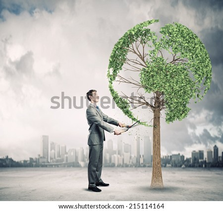 Young businessman cutting tree with scissors in shape of Earth planet