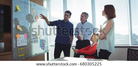 Young businessman discussing with colleagues over whiteboard at office