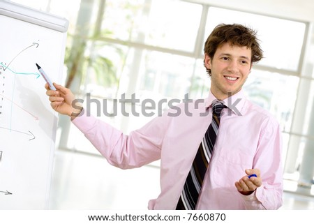 Young businessman doing presentation on whiteboard.