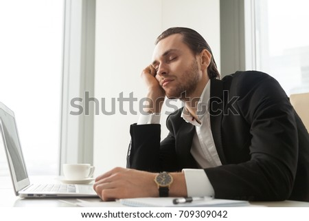 Young businessman dozed in front of laptop in office. Exhausted CEO overworked and fell asleep at workplace. Entrepreneur with heavy workload, lack of sleep, working non-stop, feeling sick at work.