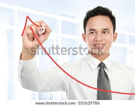 Young businessman drawing statistic arrow on screen with a pen in the office