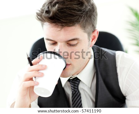 Young businessman drinking coffee in the office  against white background