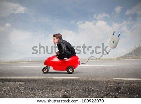 Young businessman driving an electric toy car on a road