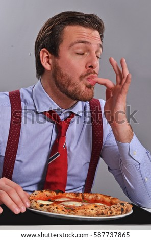 Young businessman eat pizza and slick fingers.