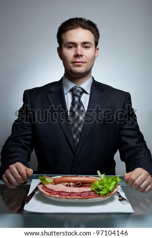 Young businessman eating. Rich meat menu.