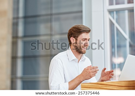 Young businessman engaged in a conversation on his laptop in a corporate setting