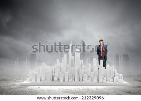 Young businessman examining model of construction project