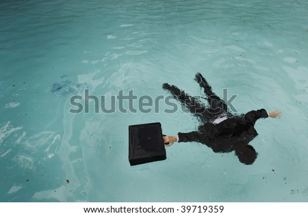 Young businessman face down in the water.