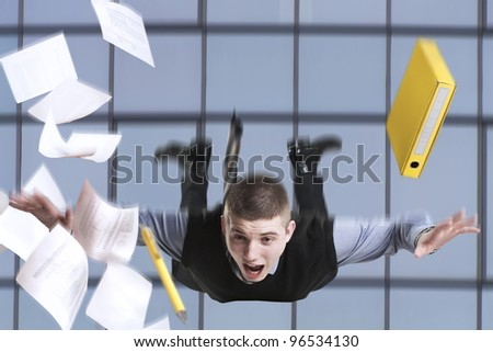 Young businessman falling from the building with his documents
