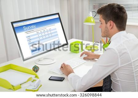 Young Businessman Filling Online Survey Form On Computer At Desk