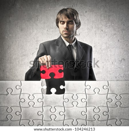 Young businessman finishing a puzzle