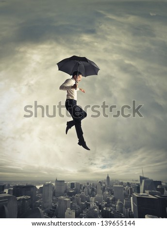 young businessman flying with umbrella over the city