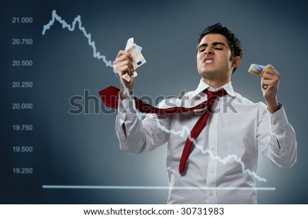 Young businessman getting mad behind a declining share. Recession and crisis concept!