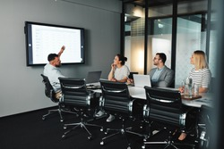 Young businessman giving a digital presentation on a monitor to colleagues during a meeting in an office boardroom