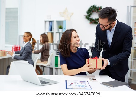 Young businessman giving his colleague Christmas present in office #345747899