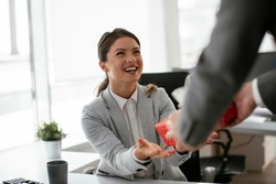 Young businessman giving his colleague present in office. Young man surprise beautiful businesswoman in office.