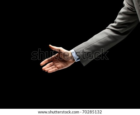 Young businessman greeting with handshake isolated on black