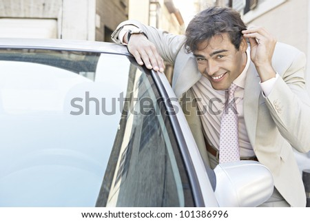 Young businessman grooming himself in the mirror of a parked car in the city.