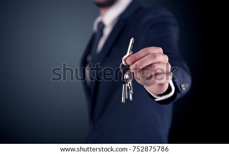 Young businessman hand over keys with empty dark background