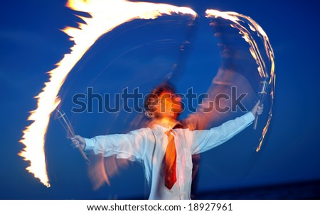 Young businessman handling flaming torch in night