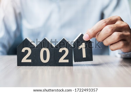 Young Businessman hands holding 2021 Happy New Year with house model on table office. New House, Financial, Property insurance, real estate, savings and New Year Resolution concepts