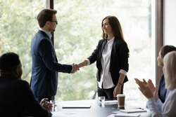 Young businessman handshake happy female colleague or employee congratulate with job success. Smiling diverse businesspeople shake hands get acquainted greeting at office meeting. Cooperation concept.