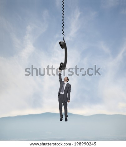 young businessman hanging on the telephone handset over the landscape