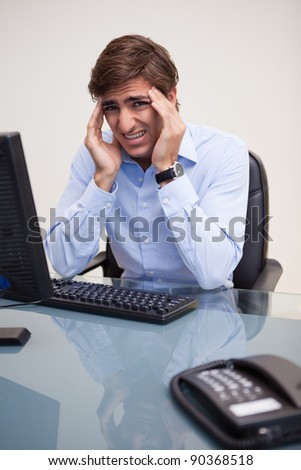 Young businessman having a headache in his office