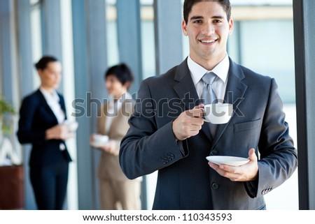 young businessman having coffee break in office