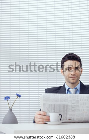 Young businessman having coffee break, sitting at office desk and reading newspaper. Copy space.