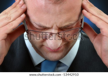 Young businessman having headache, close up image