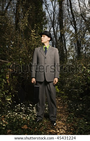 Young businessman holding a black briefcase in the woods looking pensively into the forest. Vertical shot.