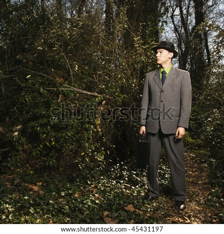Young businessman holding a black briefcase in the woods looking pensively into the forest. Square format.