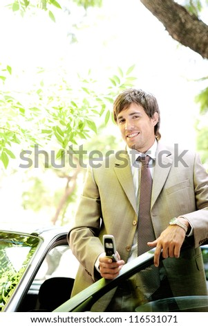 Young businessman holding a cell phone while leaning on his car door while in a leafy street.