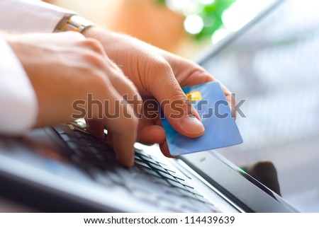 Young businessman holding a credit card and typing. On-line shopping on the internet using a laptop