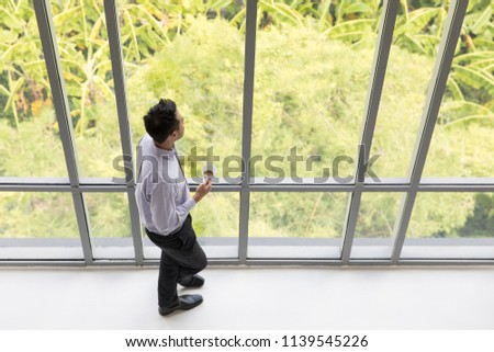 Young businessman holding a cup of coffee standing by the window looking away, with a green tree as a background.