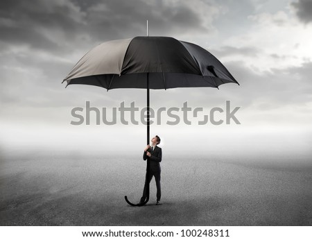 Young businessman holding a giant umbrella under stormy sky