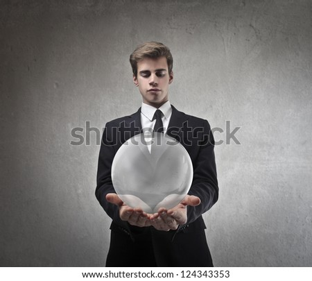 Young businessman holding a glass bubble
