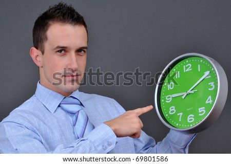 young businessman holding a green clock over grey