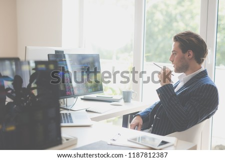 Young businessman holding a pencil while working with stocks on a laptop and on a desktop computer.