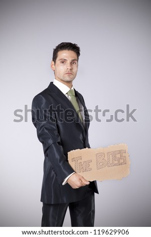 young businessman holding a piece of cardboard saying that he is the boss