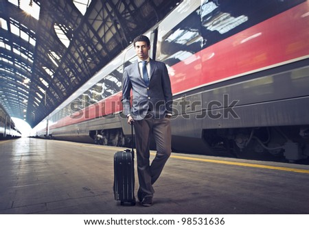 Young businessman holding a suitcase on the platform of a train station - stock photo