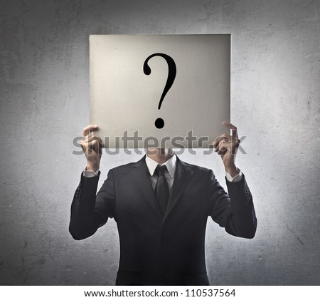 Young businessman holding a white billboard with a question mark on it
