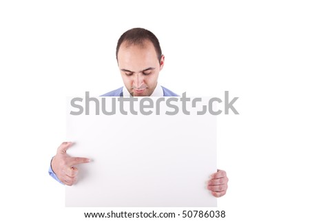 Young businessman holding a white board and pointing, looking down, isolated on white background