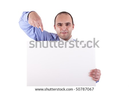 Young businessman holding a whiteboard and pointing, looking at the camera, isolated on white background