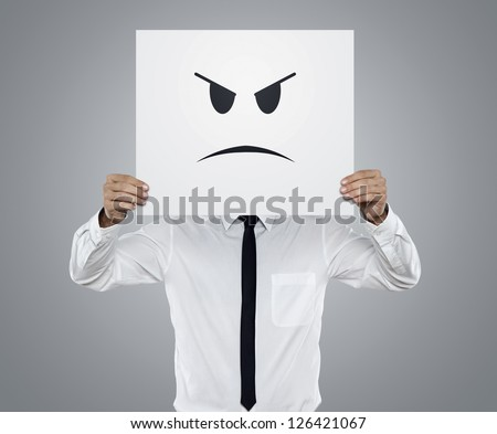 Young businessman holding card with a angry face on it isolated on gray background