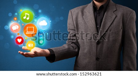 Young businessman holding colorful multimedia icons in his hand